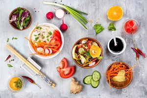 Cooking assorted vegetable salads and asian dish on stone background,
