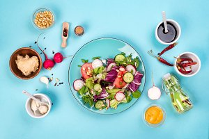 Healthy eating concept with fresh vegetables and salad bowls on kitchen wstone worktop,