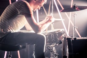 pensive man playing the drums. Against the background of colored lights and a bright beam of light.
