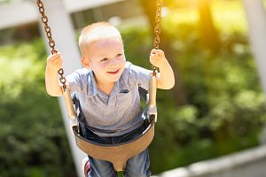 Young Boy Having Fun On The Swings