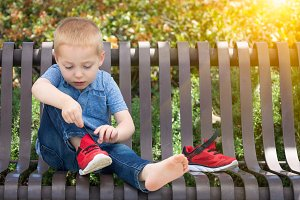 Young Boy On Bench Putting Shoes On