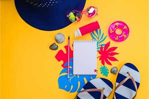Header with traveling essentials from above. Vacation concept with tropical leaves, beach sandals, sunglasses and a notepad with blank pages on a vibrant yellow background with copy space.