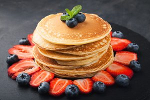 Delicious pancakes close up, with fresh blueberries, strawberries on a black stone background