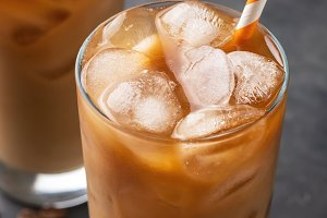 Ice coffee in a tall glass with cream poured over, brown sugar and coffee beans. Cold summer drink on a dark background