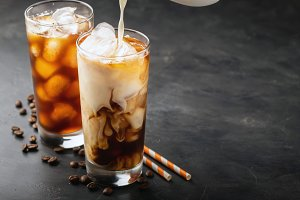 Ice coffee in a tall glass with cream poured over, brown sugar and coffee beans. Cold summer drink on a dark background. With copy space