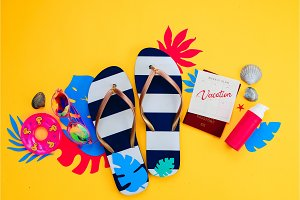 Summer holiday concept, travel and beach accessories with copy space. Flip flops, tropical leaves and a calendar with Vacation note on a vibrant yellow background.