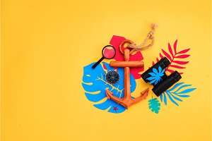 Summer vacation flat lay with beach accessories and tropical leaves on a vibrant yellow background. Travel essentials from above with copy space. Modern colorful palette.