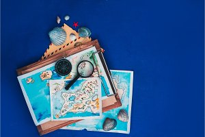 Sea travel and exploration concept. Watercolor maps on a wooden clipboard, compass and magnifying glass flat lay on a navy blue background with copy space