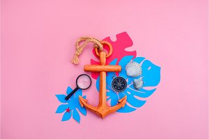 Colorful travel and vacation concept on a bright pink background. Tropical leaves, wooden anchor, compass and sea shells with copy space.