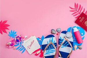 Header with flip flops, sunglasses and sunscreen on a vibrant pink background with copy space. Feminine summer vacation essentials concept. Colorful travel flat lay with tropical leaves.