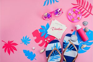 Feminine summer vacation essentials concept. Flip flops, sunglasses and sunscreen on a vibrant pink background with copy space. Colorful travel flat lay with tropical leaves.