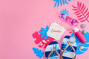 Feminine summer vacation essentials header. Colorful travel flat lay with tropical leaves. Flip flops, sunglasses and sunscreen on a vibrant pink background with copy space.