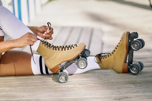 Girl sitting puts on skates outdoors