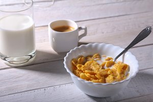 Corn Flakes cereal in a bowl, glass with milk and cap with espresso coffee. Morning breakfast.