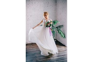 young beautiful bride smiling and spinning in the loft