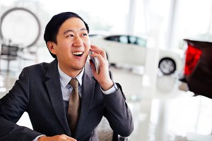 Portrait of happy and smiling Businessman holding and confidently talking on the phone in car showroom scene