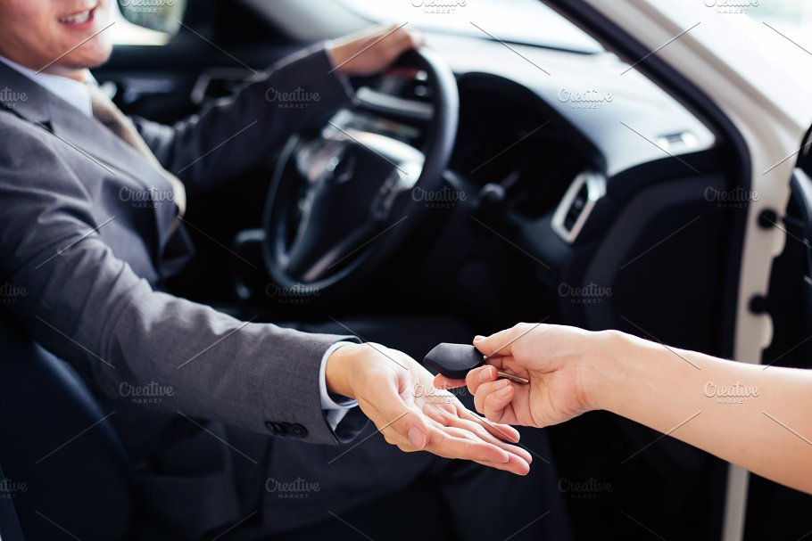 Smiling And Happy Man Receiving A Car Key From Car Dealer Salesman