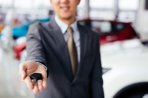 Smiling and happy car dealership or rental service business salesman in suit giving a car key to new buyer in showroom and bunch of cars scene background