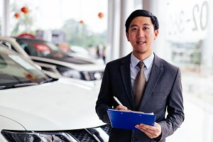 Young Asian business salesman holding a notepad to welcome clients into car showroom