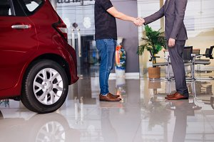 Businessman in formal suit handshaking with other partner in car background in showroom - successful partnership and deal concept