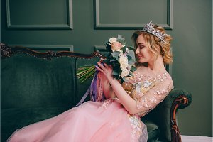 woman sits on a vintage couch and looks at the bouquet in her hands