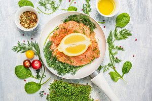 Salmon in white pan with greens