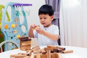 Asian child playing with wooden blocks in the room at home. A kind of educational toys for preschool and kindergarten kids
