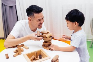 Asian child and father playing with wooden blocks in the room at home. A kind of educational toys for preschool and kindergarten kids