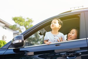 Happy Asian family is looking up in the sky and travelling on the road trip, going for a drive for vacation