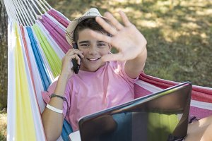 child in hammock with computer and m