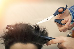 hands with hairdressing scissors cut
