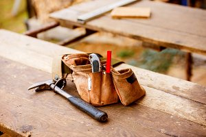 Carpenters bag with belt full of tools, wooden table