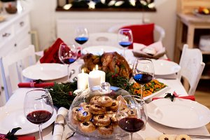 Christmas meal laid on table in decorated dining room.