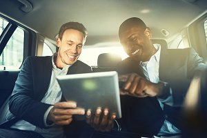 Smiling business colleagues working online together in a car backseat