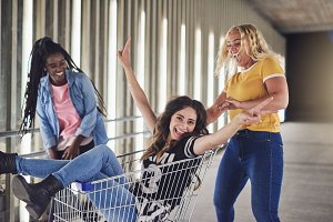Girlfriends having fun with a shopping cart at night