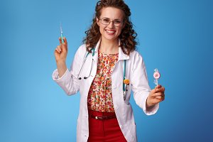 smiling pediatrist doctor with syringe and lollypop on blue