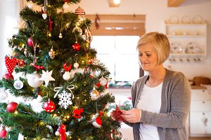 Senior woman at home decorating Christmas tree.