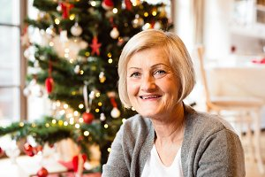 Senior woman in front of illuminated Christmas tree.