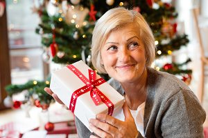 Beautiful senior woman in front of Christmas tree with present