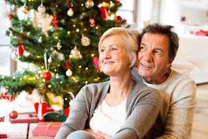 Senior couple in front of Christmas tree hugging, close up.