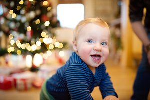 Little boy at home against Christmas tree and presents
