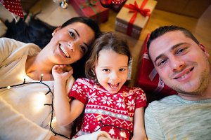 Young family lying under Christmas tree among presents,