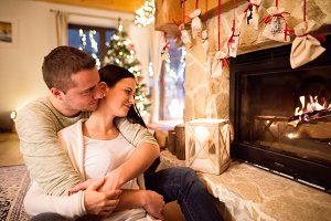 Couple in front of fireplace. Christmas tree behind them.