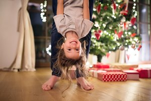 Father with daugter at Christmas tree holding her upside down.