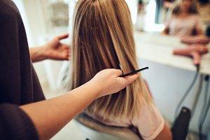 Woman getting her hair cut by a salon hairstylist