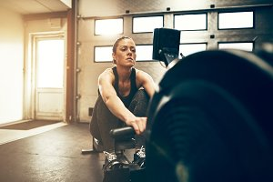 Fit young woman using a rowing machine at the gym