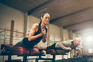 Two fit people working their cores on gym benches
