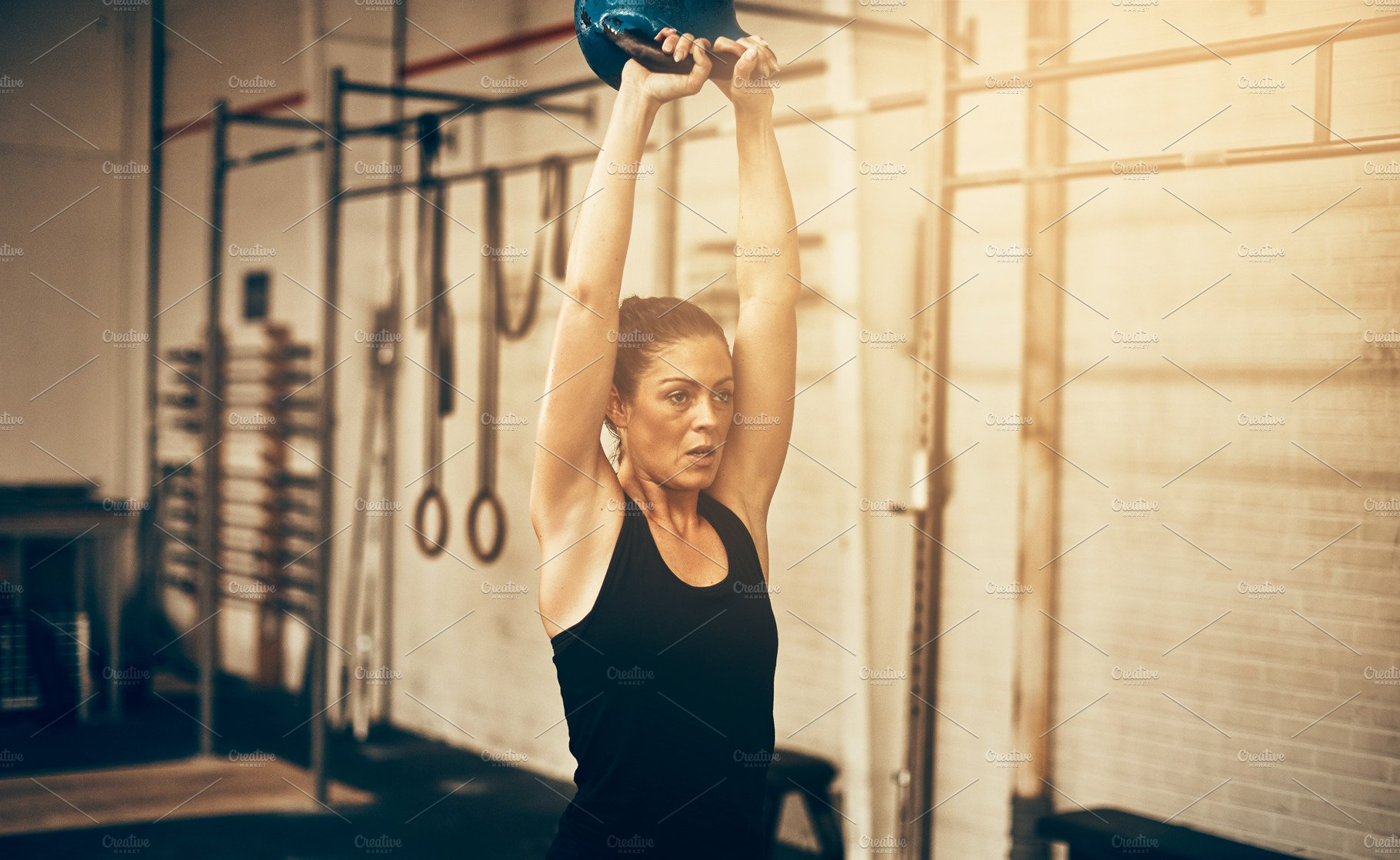 Focused young woman swinging a dumbbell at the gym ~ Sports Photos ~  Creative Market