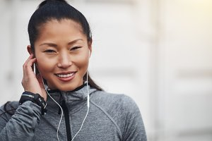 Sporty young Asian woman listening to music before a jog