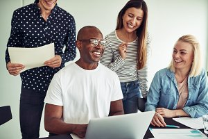 Diverse group of businesspeople laughing together in an office